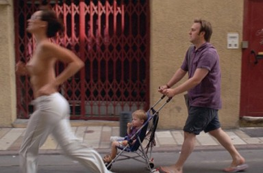 topless woman running man pushing baby